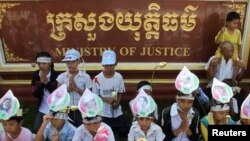 Children of women who were arrested in clashes with police during forced evictions at Boeung Kak lake, wear portraits of their mothers around their foreheads as they pray at a protest in front of the Ministry of Justice in the capital of Phnom Penh, file photo.