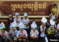 FILE - Children of Boeung Kak women protesters wear portraits of their mothers around their foreheads as they pray at a protest in front of the Ministry of Justice in Phnom Penh.