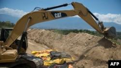 Petugas menggunakan alat berat untuk membuat kuburan massal bagi korban gempa dan tsunami di Palu, Sulawesi Tengah.