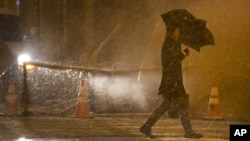 A pedestrian walks into the wind and snow in the financial district, in New York, November 7, 2012.