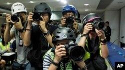 Phóng viên nhiếp ảnh đội mũ bảo hộ ghi hình cuộc họp báo của cảnh sát trưởng Stephen Lo ở Hong Kong hôm 13/6. (AP Photo/Vincent Yu)