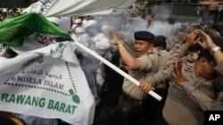 Polisi melemparkan gas air mata untuk membubarkan demonstran yang memrotes film 'Innocence of Muslims' di depan Kedutaan Besar AS di Jakarta, Senin (17/9).