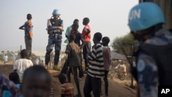 FILE - A United Nations peacekeeper stands with displaced children on a wall around the United Nations base in the capital Juba, South Sudan.