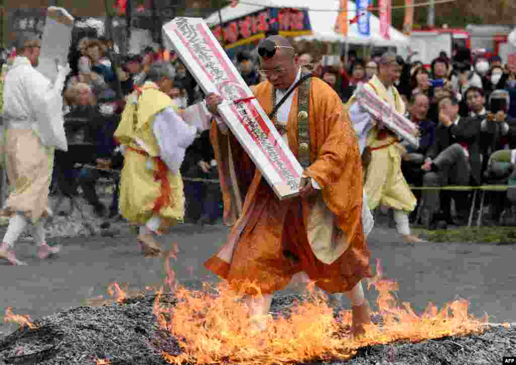 "Carrying a talisman, a Buddhist ascetic walks barefoot among flames on hot coals during the ""Hi-Watari"", or fire walking ceremony, to herald the coming of Spring at the Fudoji temple in Nagatoro town in Saitama prefecture, Japan."