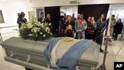 People stand in front of the coffin of Argentine folk singer Facundo Cabral during his funeral service at the ND Ateneo theater in the center of Buenos Aires, July 12, 2011