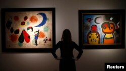 """An employee at Christie's poses with Joan Miro's """"L'Oiseau au plumage deploye vole vers l'arbre argente"""" (R) and """"Painting (Women, Moon, Birds)"""" in London, Jan. 8, 2015."""