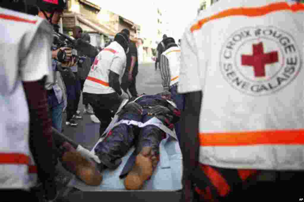 A young woman injured in violent clashes between police and anti-government protesters is transported to an ambulance by emergency responders from the Senegalese Red Cross, in central Dakar, Senegal Friday, Feb. 17, 2012. Anti-government protesters and po
