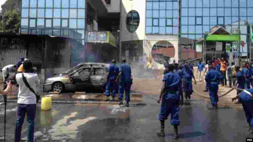 Igisasu cya gerenade cyaturikiye hanze y'inzu Kenya Commercial Bank ikoreramo I Bujumbura. Imodoka eshatu na moteri itanga amashanyarazi byahiye.(Edward Rwema / VOA)