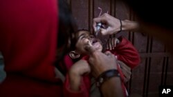 FILE - A Pakistani child receives a polio vaccine by a health worker in Islamabad, Nov. 26, 2013.