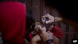 Seorang anak Pakistan mendapatkan vaksin polio dari petugas kesehatan di Islamabad, 26 November 2013.