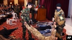 """Iraqi students act out a scene in a play titled """"We are all against terrorism"""" at Mansour Hotel in Baghdad, May 6, 2015."""