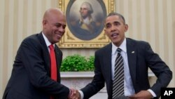 President Barack Obama and Haiti President Michel Martelly shake hands during a photo opportunity in the Oval Office of the White House in Washington, Feb. 6, 2014.