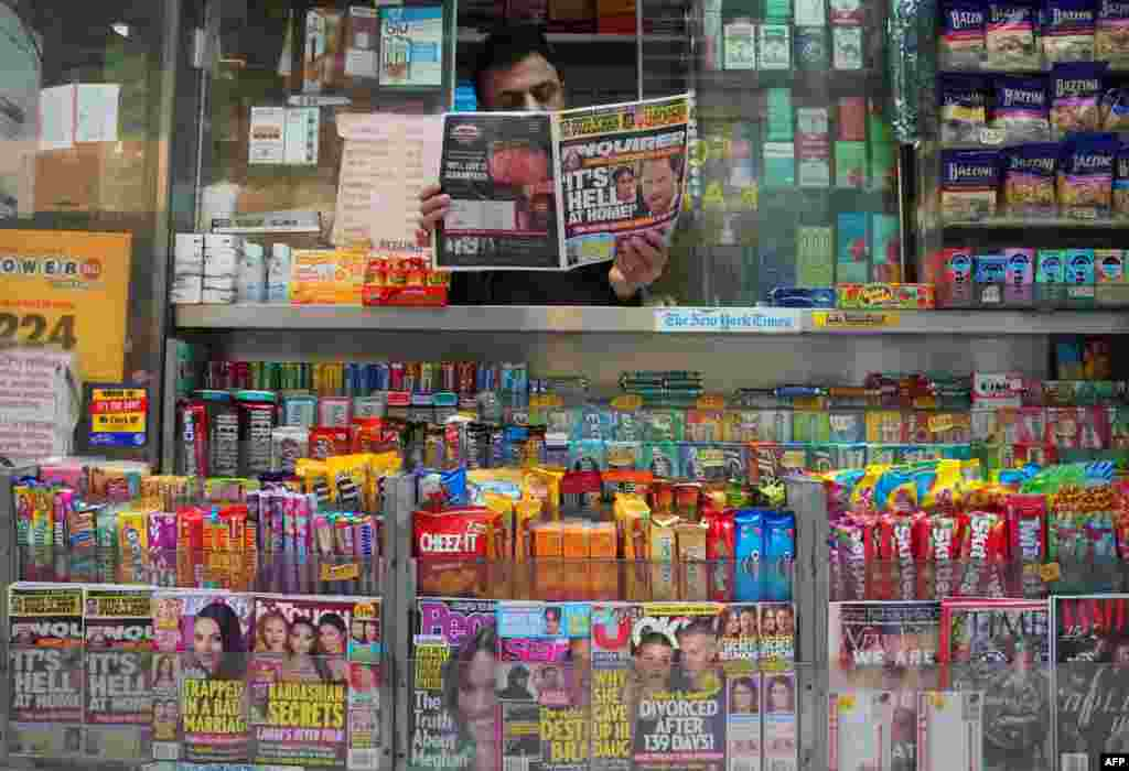 A newspaper vendor on Third Avenue in midtown New York City displays a copy of the National Enquirer for a photographer at his news stand. The publisher of the National Enquirer said Friday it would open an internal probe of accusations by Amazon's Jeff Bezos over blackmail and extortion by the tabloid.