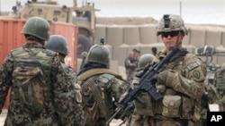 Afg'on zobitlari (chapda) AQSh askarining yonidan o'tib ketmoqda. Kobul, Afg'oniston, 11-mart, 2012-yil.