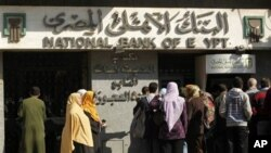 Egyptians wait at an automatic cash dispenser (ATM) in Cairo, Egypt, February 2, 2011