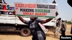A woman holds a placard during a rally to show support for Nigeria's President Muhammadu Buhari in Abuja, Nigeria, Feb. 6, 2017.