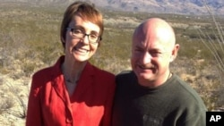 In this photo provided by the office of U.S. Rep. Gabrielle Giffords, Giffords and husband Mark Kelly pose at the Davidson Canyon Gabe Zimmerman Memorial trailhead outside of Tucson, Arizona, January 7, 2012.