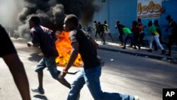 Protesters run past a barricade to a nearby depot that was being looted, during a protest demanding the resignation of President Jovenel Moise in Port-au-Prince, Haiti, Feb. 11, 2019.