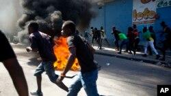 Los manifestantes pasan por una barricada cercana a un depósito que estaba siendo saqueado, durante una protesta, en Haití.