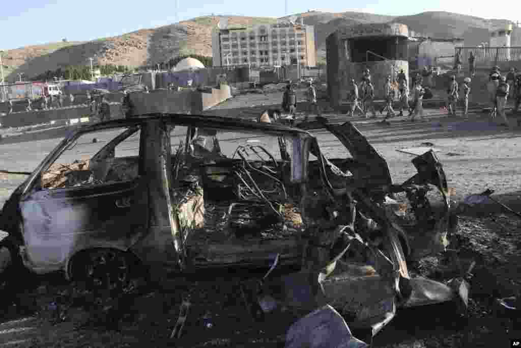 Afghan security personnel investigate a suicide car bombing and a gunfight near the U.S. consulate in Herat, Afghanistan, Sept. 13, 2013.
