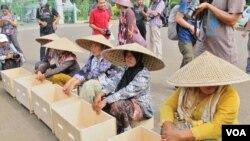 Sembilan perempuan asal Pegunungan Kendeng, Jawa Tengah Selasa (12/4) sore unjuk rasa di depan Istana Negara, menolak pembangunan pabrik semen di wilayah mereka (VOA/Fathiyah).