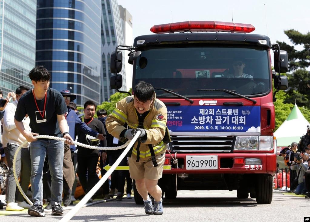 한국 서울에서 열린 '서울 안전한 마당'에서 소방관이 줄을 사용하여 소방차를 끌고 있다.