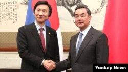 왕이 중국 외교부장(오른쪽)이 지난해 4월 베이징에서 윤병세 한국 외교장관의 회담에 앞서 악수를 나누고 있다. (자료사진)