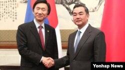지난달 중국을 방문한 윤병세 한국 외교부 장관과 왕이 중국 외교부장과 회담에 앞서 악수를 나누고 있다. (자료사진)