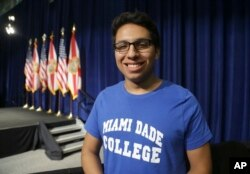 FILE - Miguel Zamudio poses for before an event where President Barack Obama spoke about the Affordable Care Act, at Miami Dade College, in Miami. Zamudio volunteers for the Democratic presidential nominee Hillary Clinton. Millennials like him are considered key in this election, not only because of their votes, but they motivate other Latinos to register and go to the polls.