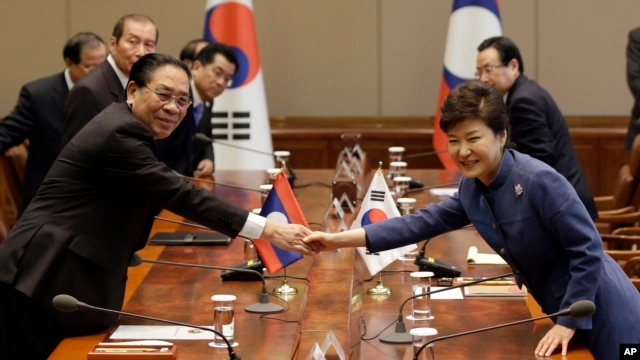 Lao President Choummaly Sayasone, left, shakes hands with his South Korean counterpart Park Geun-hye before their meeting at the presidential Blue House in Seoul, South Korea, Nov. 22, 2013.