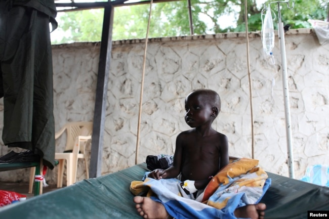 FILE - A South Sudanese child suffering from cholera sits on a bed in Juba Teaching Hospital in Juba, May 27, 2014.