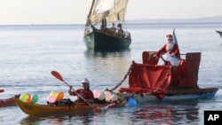 A man dressed as a Santa Claus rides a float pulled by a kayaker, on the Mediterranean sea during the traditional Christmas bath at Nice, southeastern France, Sunday, Dec. 20, 2015. (AP Photo/Lionel Cironneau)