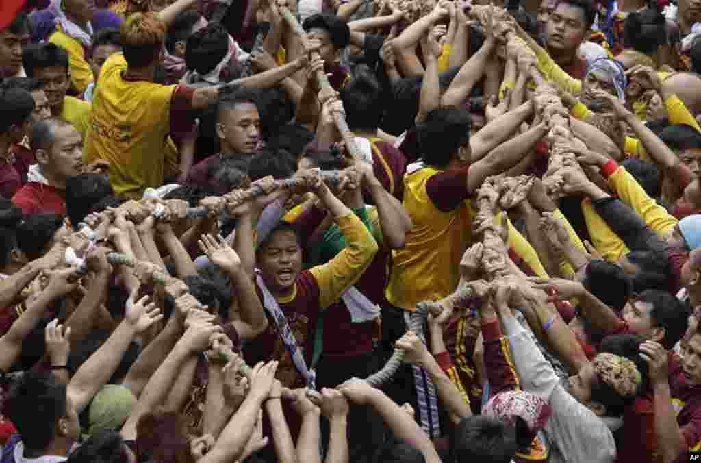 필리핀 마닐라에서 가톨릭 신자들이 '검은 예수상'을 운반하는 수레에 연결된 밧줄을 앞다투어 잡으려 하고 있다.