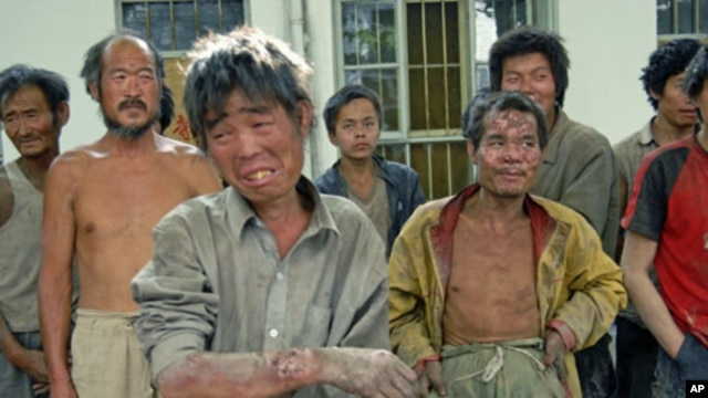 Workers forced to work as slaves -  given only bread, water and no pay - stand at a police station after they were rescued from a brickworks run by the son of a local Communist Party official, in Hongdong County in Linfen, north China's Shanxi province, M