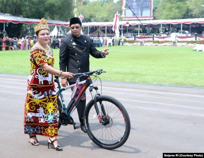 Istri Wakil Ketua MPR – Agati Sulie Mahyudin – yang mengenakan pakaian adat Dayak nampak menggandeng sepeda hadiah dari Presiden Joko Widodo (Courtesy: Setpres RI)