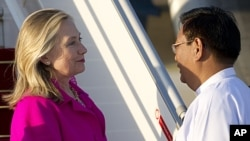 US Secretary of State Hillary Clinton is greeted by Burma's Deputy Foreign Minister Myo Myint upon her arrival in Naypyidaw, November 30, 2011.