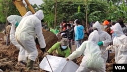 A mortuary team in full hazmat suits lowers the casket of a COVID-19 victim at a special cemetery in TPU Rorotan, north Jakarta, Indonesia, July 8, 2021. Some 200-400 bodies get buried there per day. (Indra Yoga/VOA Indonesian)
