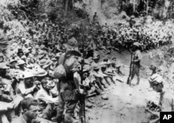 FILE - In this 1942 file photo provided by U.S. Marine Corps, Japanese soldiers stand guard over American war prisoners just before the start of the Bataan Death March following the Japanese occupation of the Philippines.