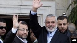Perdana Menteri Gaza Ismail Haniyeh (kanan) dan Perdana Menteri Mesir Heshan Kandil (kiri) melambaikan tangan ke para hadirin saat bertemu di Kota Gaza (16/11). Israel menawarkan diri untuk menghentikan serangan di Gaza selama kunjungan PM Mesir ke negaranya hari ini.