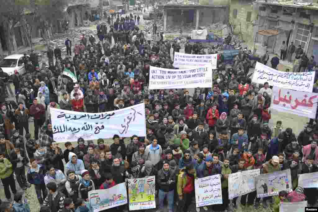 Demonstrators hold banners during a protest against Syria's President Bashar al-Assad, after Friday prayers in Kafranbel, near Idlib, Syria, January 11, 2013 in this picture provided by Shaam News Network.