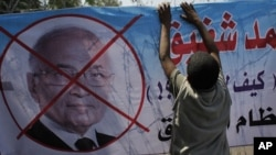 """An Egyptian youth hangs a banner with a defaced picture of presidential candidate, Ahmed Shafiq and Arabic that reads """"Shafiq, the former regime,"""" during a protest in front the Supreme Constitutional Court in Cairo, Egypt, June 14, 2012."""