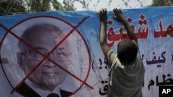 "An Egyptian youth hangs a banner with a defaced picture of presidential candidate, Ahmed Shafiq and Arabic that reads ""Shafiq, the former regime,"" during a protest in front the Supreme Constitutional Court in Cairo, Egypt, Thursday, June 14, 2012."