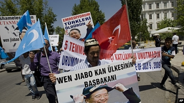 "Uighurs living in Turkey hold a poster of Chinese Prime Minister Wen Jiabo with a banner that reads "" the premier of the country of blood"" as they march to the Chinese embassy in Ankara, Turkey, July 5, 2011"