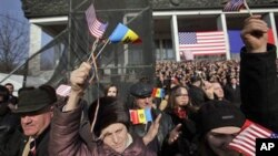 Moldovans wave American flags as US Vice President Joseph Biden speaks to several thousand people on a central square in Chisinau, Moldova, March 11, 2011