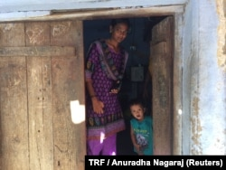 Poomalai Poomari and her niece at the door of their one-room home in Ayanapuram village in Tamil Nadu, India. July 27, 2017.