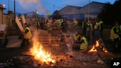Demonstrators stand in front of a makeshift barricade set up by the so-called yellow jackets to block the entrance of a fuel depot in Le Mans, western France, Tuesday, Dec. 5, 2018. (AP Photo/David Vincent)