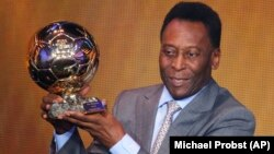 La légende du football brésilien Pelé exhibe le prix d'honneur qu'il a reçu à la FIFA Ballon d'Or 2013 Gala à Zurich , Suisse , le lundi 13 janvier, 2014. (AP Photo / Michael Probst )
