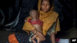 Seorang perempuan Muslim Rohingya menggendong bayinya berusia 10-bulan di kamp pengungsi Thaingkhali, Bangladesh, Sabtu (21/10) lalu.