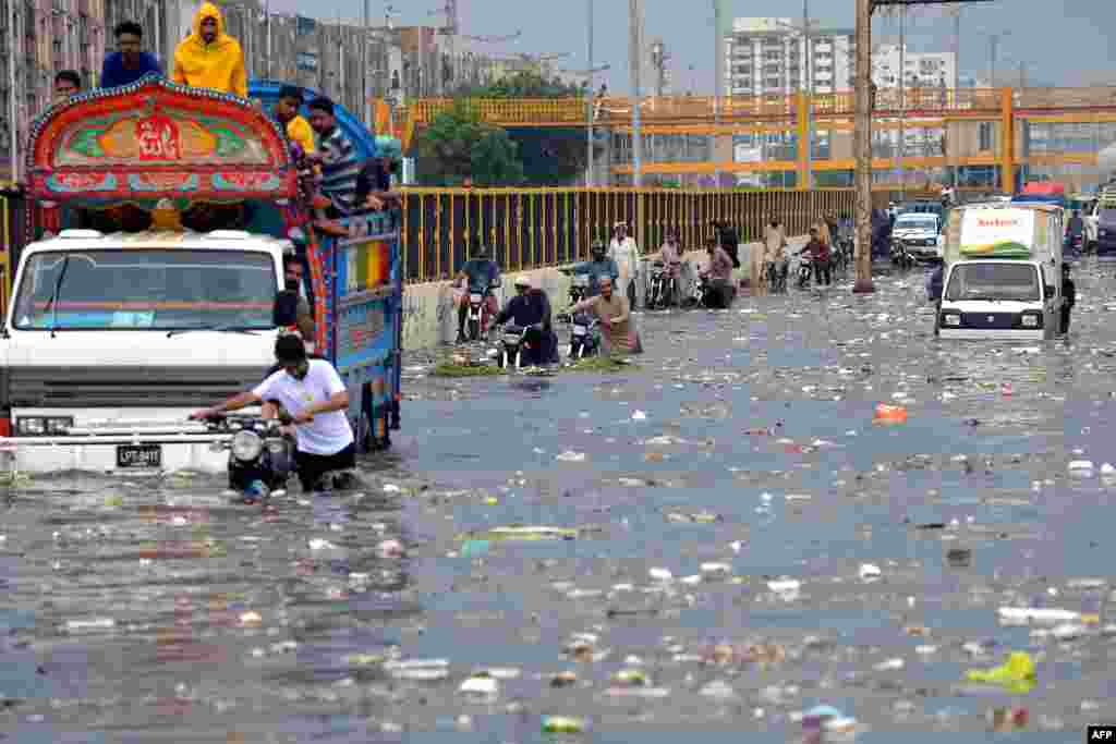 People wade through a flooded street after heavy monsoon rains in Karachi, Pakistan.