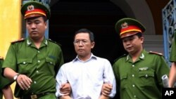 FILE - Police officers escort French-Vietnamese math professor Pham Minh Hoang out of a courthouse in Ho Chi Minh City, Aug. 10, 2011.